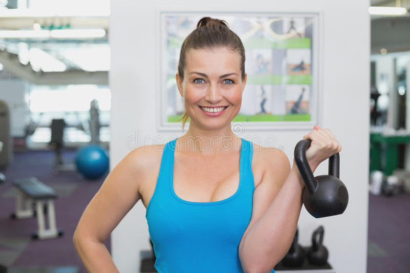 Fit brunette working out with kettlebell stock photography