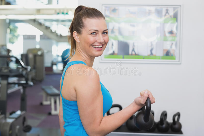 Fit brunette working out with kettlebell stock photos