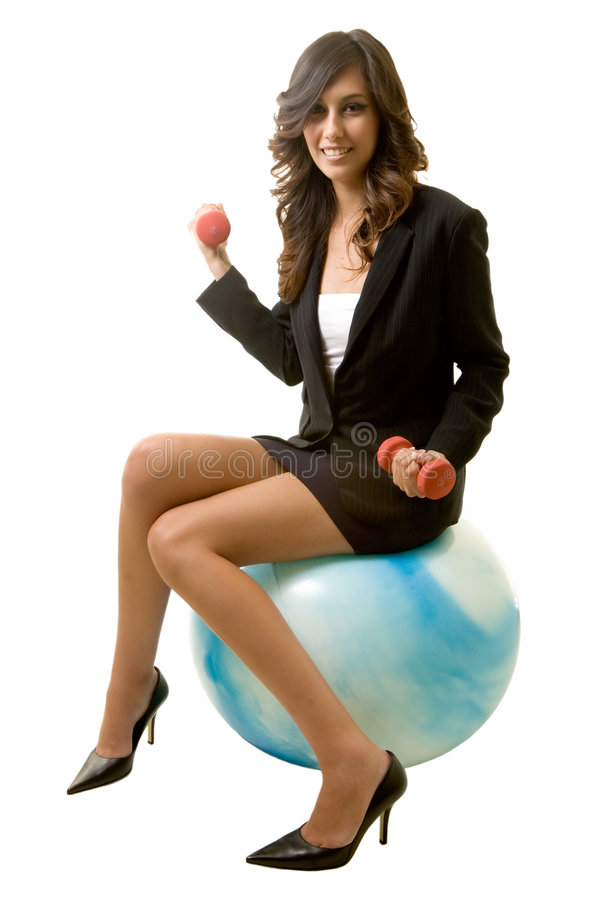 Fit business woman. Attractive brunette smiling business woman sitting on a blue workout ball holding weights wearing black business suit on white stock images