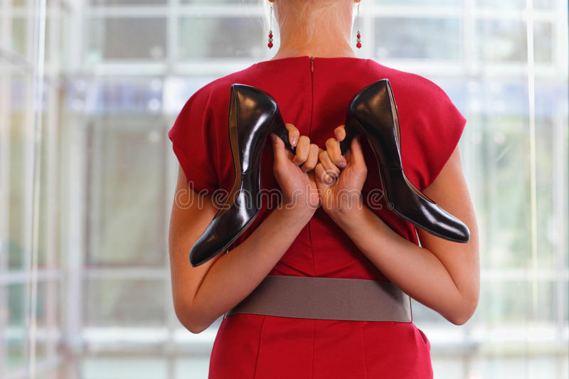 Fit business woman in dress with two high heels stock photography