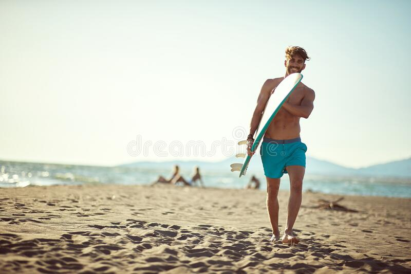 Fit caucasian beardy male walking on the sunny beach, holding surfboard, smiling royalty free stock photo