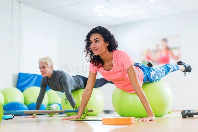 Fit Caucasian female athletes in sportswear doing Pilates exercises with fitness ball in sports club royalty free stock photography