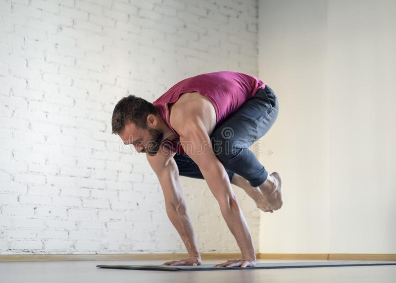 Fit caucasian man practice yoga in fitness studio, selective focus. Crane pose, bakasana. Pilates, workout, smart body, exercise therapy, flexibility, sport royalty free stock images