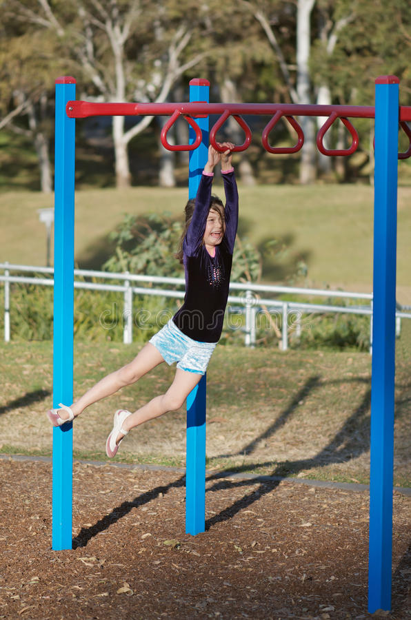 Fit child on monkey bars royalty free stock photography