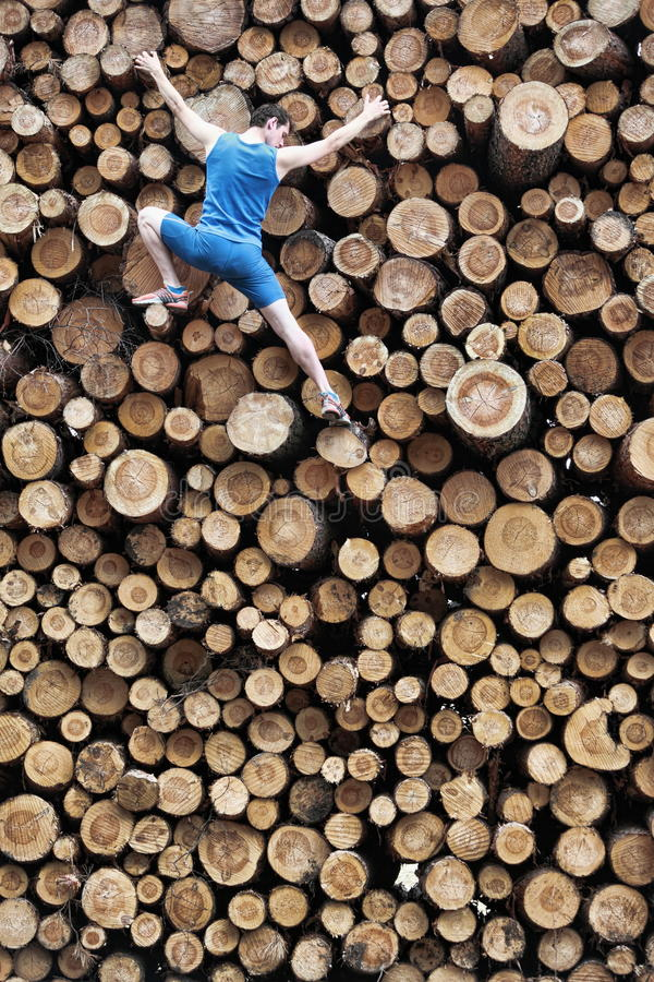 Fit climber going down the large pile of cut wooden logs. Risky hobby stock photography