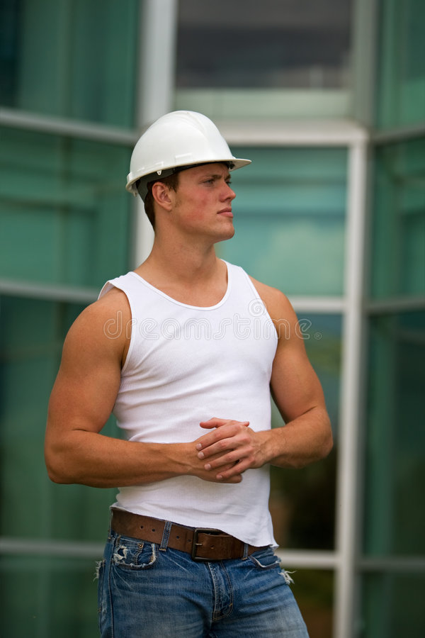 Fit construction worker. A fit construction worker in jeans and muscle shirt stock photography