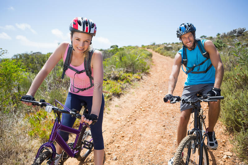 Fit couple cycling down mountain trail smiling at camera. On a sunny day royalty free stock photography
