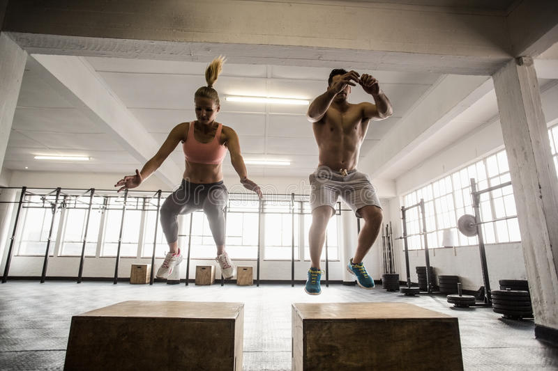 Fit couple doing set of box jumps royalty free stock photos