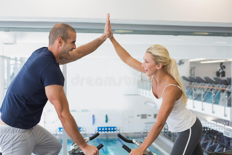 Fit couple giving high five while working on exercise bikes at gym royalty free stock photo