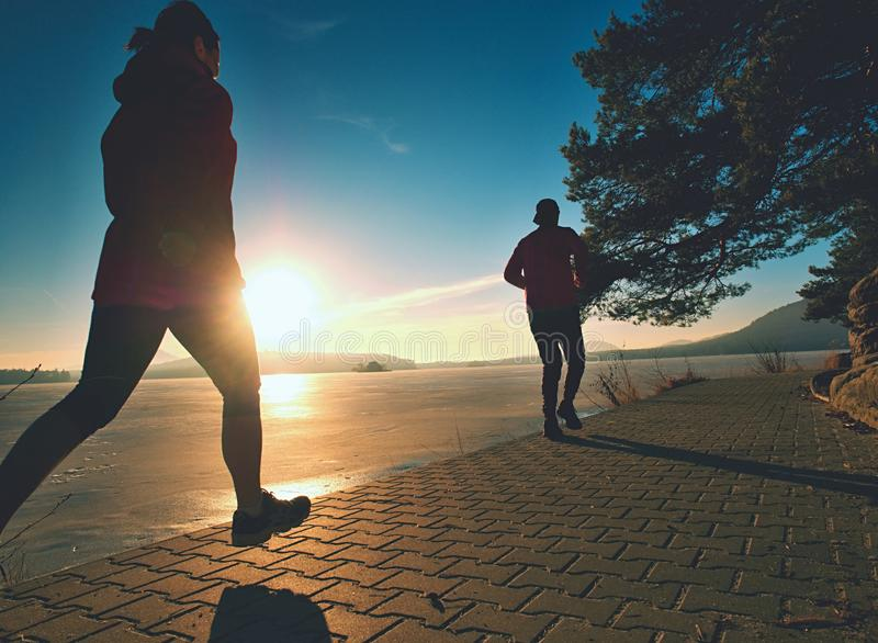 Fit couple, man and woman running along waterfront stock photo