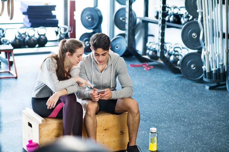 Fit couple in modern crossfit gym with smartphone. Beautiful young fit couple in modern crossfit gym talking, resting, drinking water, holding smart phone royalty free stock photos