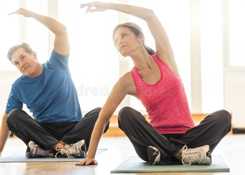Fit Couple Practicing Yoga On Mat At Home royalty free stock images