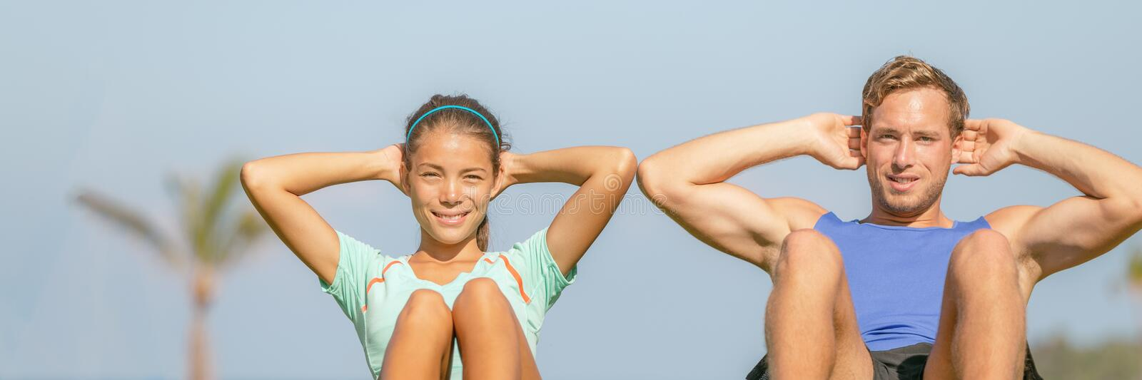 Fit couple training abs workout exercising at fitness gym panoramic banner with blue sky background. Asian woman, Caucasian man. Fit couple training abs workout stock photography