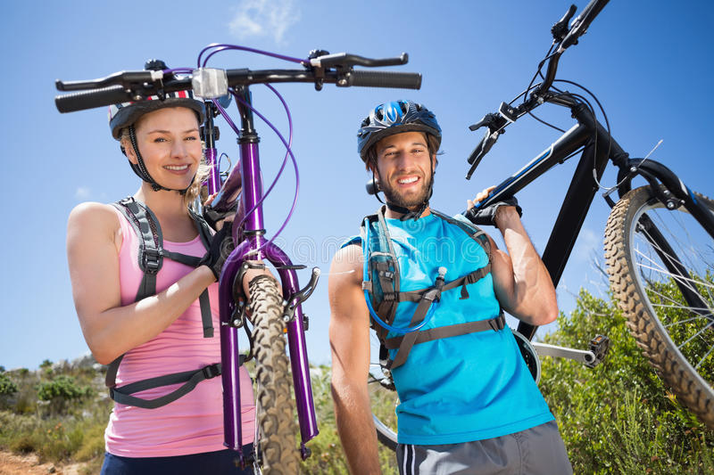 Fit couple walking down trail smiling at camera holding mountain bikes. On a sunny day stock photo
