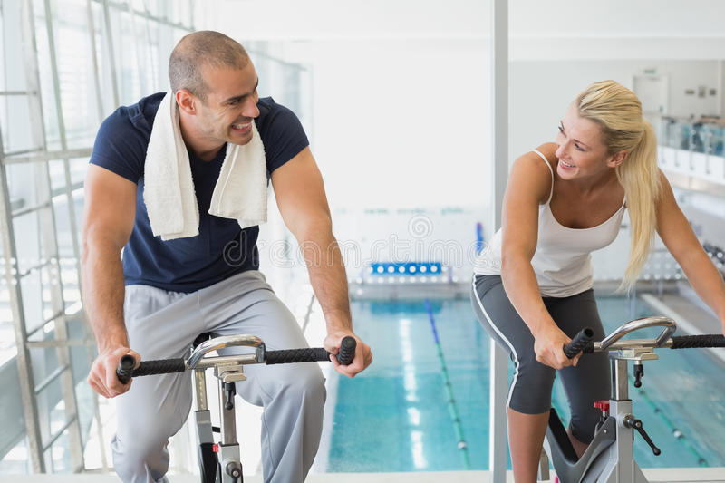 Fit couple working on exercise bikes at gym. Portrait of a fit young couple working on exercise bikes at the gym stock photos