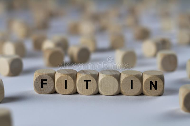 Fit in - cube with letters, sign with wooden cubes. Series of images: cube with letters, sign with wooden cubes royalty free stock image