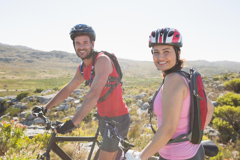 Fit cyclist couple smiling at camera on mountain trail. On a sunny day royalty free stock photos