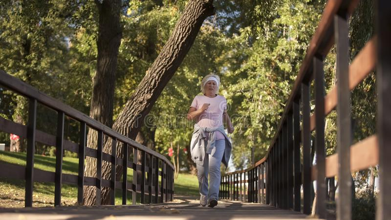 Fit elderly woman running in park, soul youth morning exercise and health royalty free stock photo