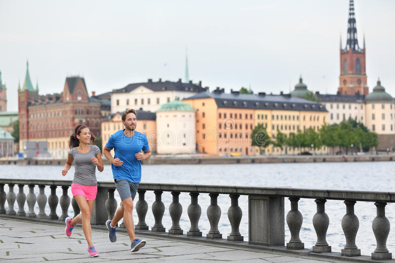 Fit exercise people running in Stockholm, Sweden. Fit fitness exercise people, healthy runners running in Stockholm city cityscape skyline. Riddarholmskyrkan royalty free stock photography