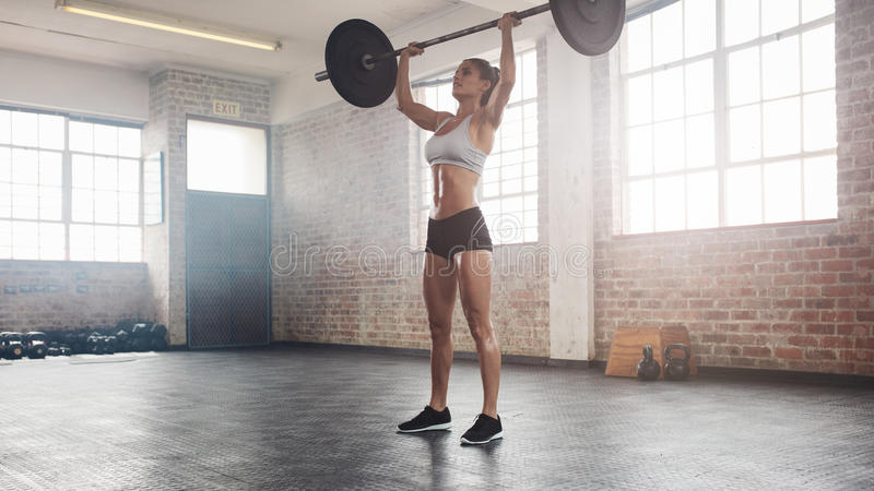 Fit female athlete doing heavy weight lifting stock photo
