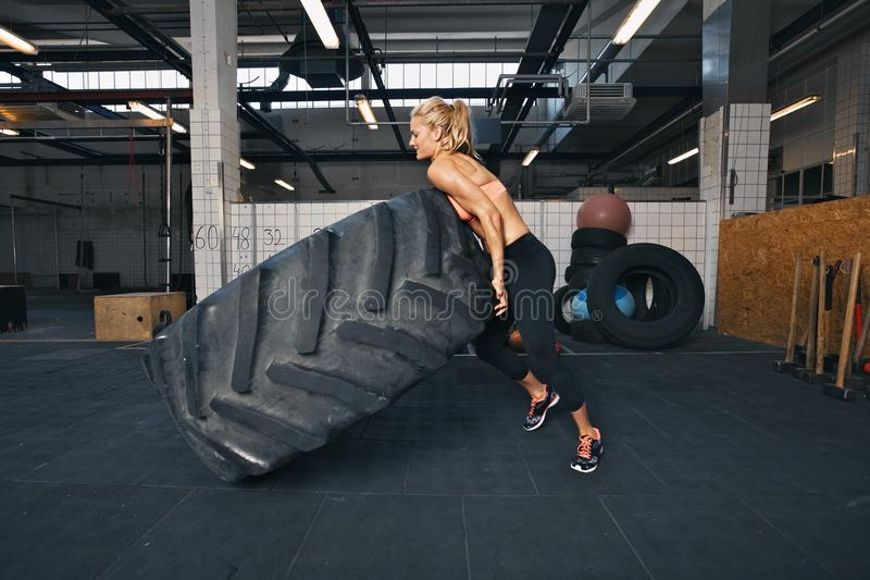 Fit female athlete flipping a huge tire. Muscular young woman doing crossfit exercise at gym stock image