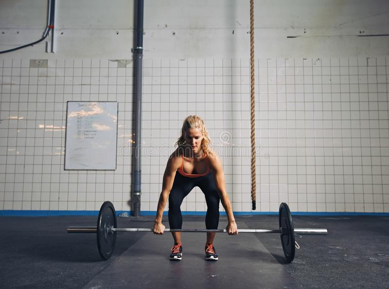 Fit female athlete performing a deadlift. Strong young woman lifting heavy weights at gym. Fitness female doing crossfit workout stock image
