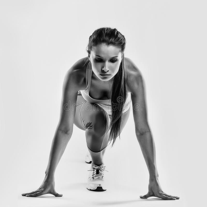 Fit female athlete ready to run over grey background. Female fitness model preparing for a sprint.  stock image