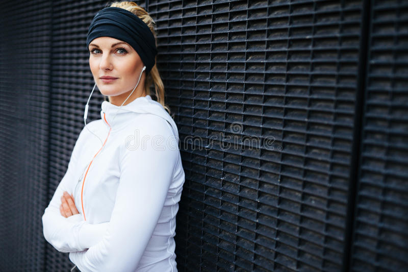 Fit female athlete taking a break for workout. Portrait of sporty young woman wearing earphones standing leaning a wall looking confidently at camera. Fit female stock image