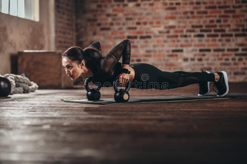 Fit female doing intense core workout in gym. Young woman doing push up exercise on fitness mat in health club royalty free stock photos