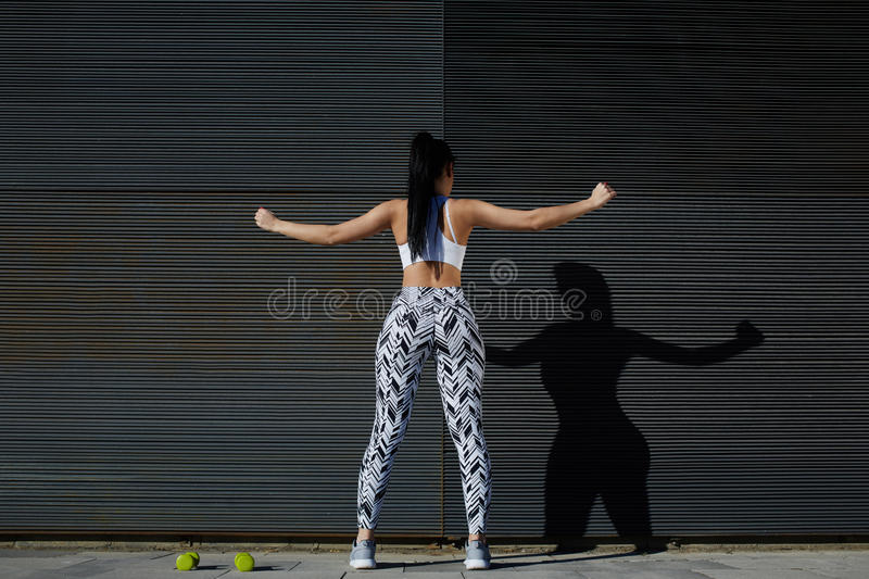 Fit female in sportswear exercising on black background outdoors. Rear view sporty woman with perfect figure and buttocks stretching her arms against wall with royalty free stock photos