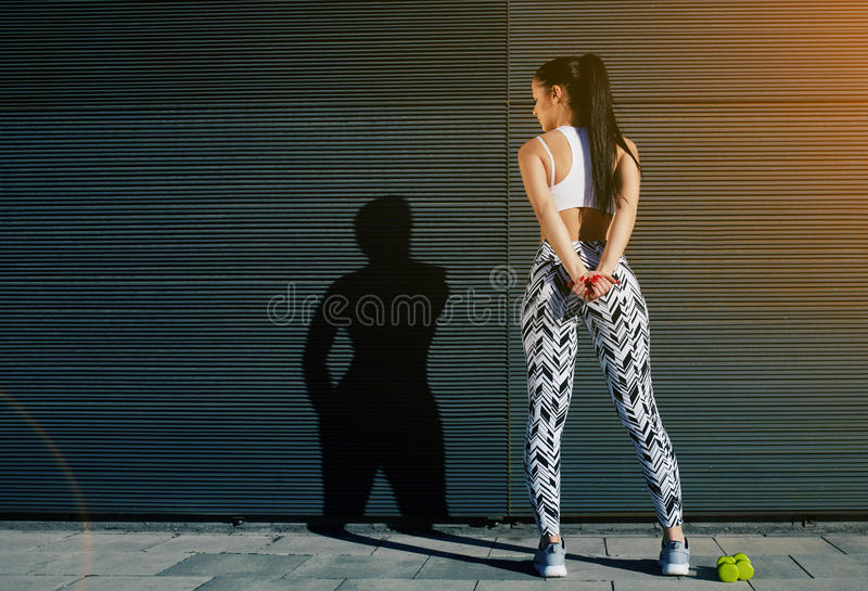Fit female in sportswear resting after training on black background outdoors. Back view athletic woman with perfect figure and buttocks taking break against wall stock photography