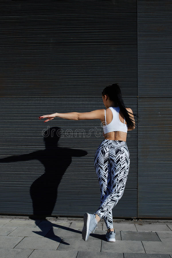 Fit female in sportswear working out while stretch on black background outdoors. Athletic woman with perfect figure and buttocks shape exercising against wall stock images