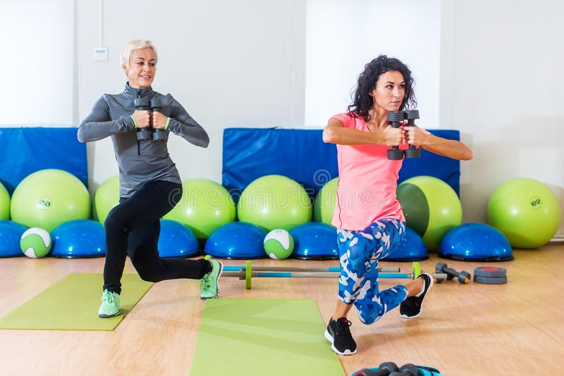 Fit female sportswoman doing curtsy lunge exercise with dumbbells in group fitness studio class.  stock photos