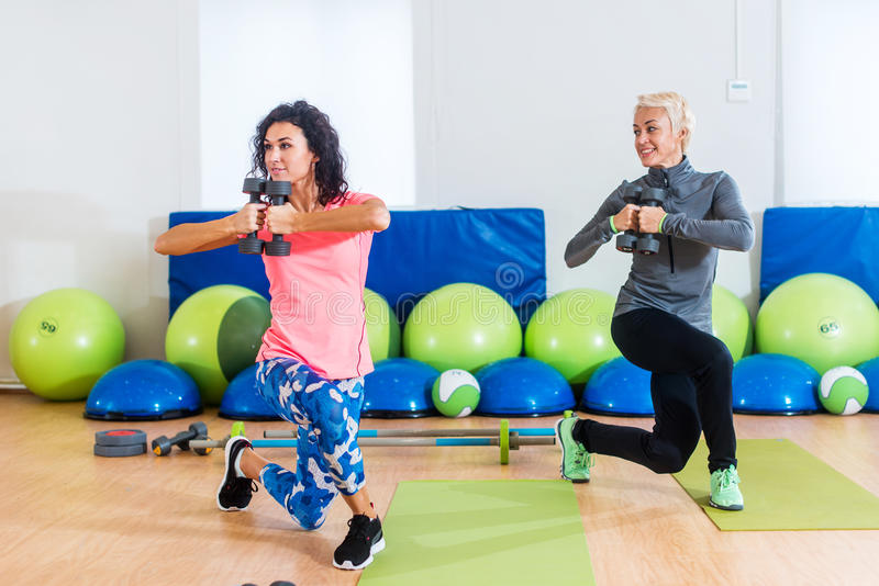 Fit female sportswoman doing curtsy lunge exercise with dumbbells in group fitness studio class royalty free stock photo