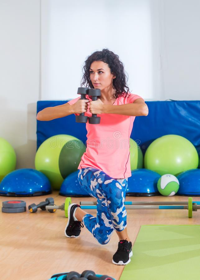 Fit female sportswoman doing curtsy lunge exercise with dumbbells in group fitness studio class.  royalty free stock photos