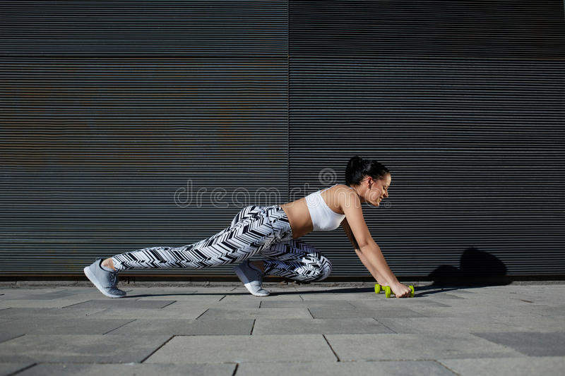 Fit female in workout gear doing push-ups on black background outdoors stock images