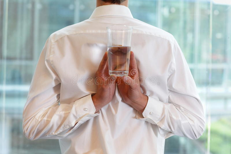 Fit flexible business man with glass of water stock photo