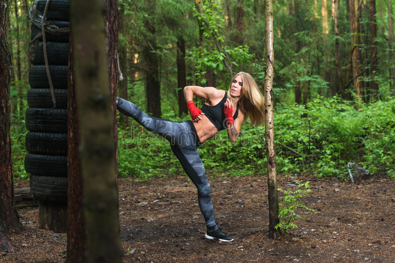 Fit girl beat high leg side kick working out outdoors. Woman fighter exercising, doing kickboxing training martial arts stock images