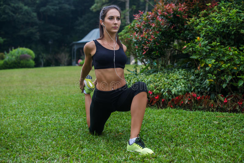 Fit girl doing kneeling quads stretch exercise in park. Young athletic woman working out and listening to music in her stock photography