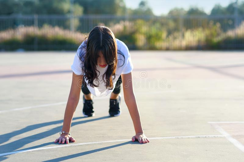 Core body workout - fitness woman doing plank. Fit girl doing plank exercise outdoor in the stadium on sunny summer day. royalty free stock photo