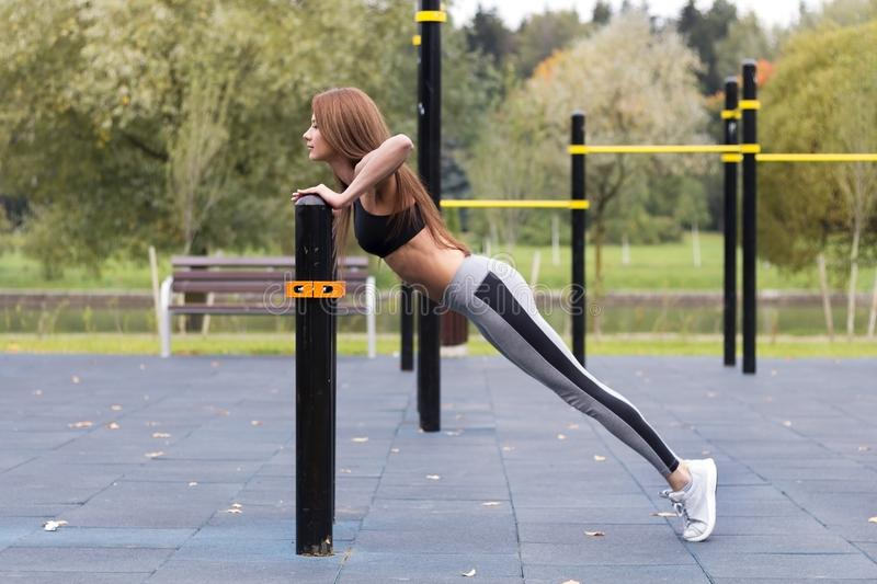 Fit girl doing plank or push-up exercise outdoor in the park warm summer day. Concept of endurance and motivation.  royalty free stock photos