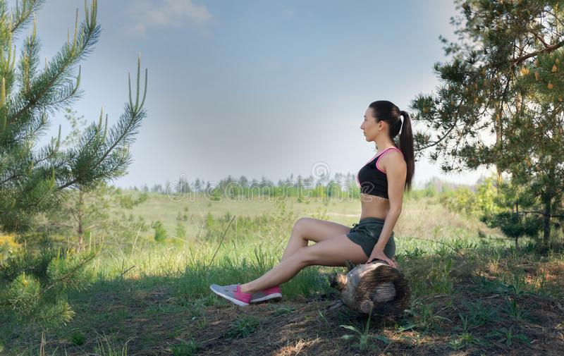 Fit girl resting in nature royalty free stock photography