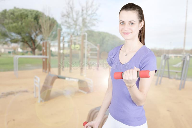 Fit girl sporty slim portrait with dumbbell in exercise outdoor royalty free stock images