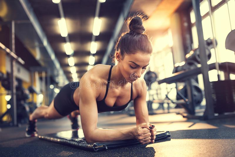 Girl training plank in gym royalty free stock photography