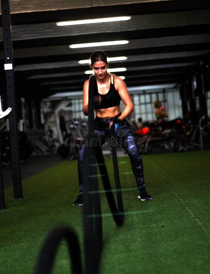 Fit girl working out with black rope in the gym royalty free stock photography