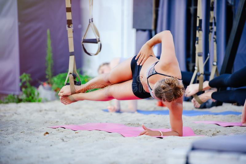 Fit girls in the gym doing exercises on the board for the spinal column and posture. Beautiful young sports people work with TRX i. N nature stock photo