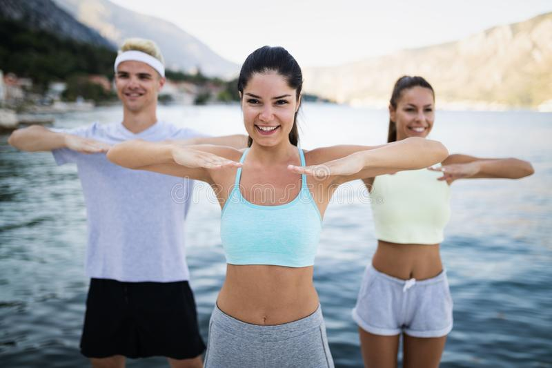 Fit group of happy people exercising outdoor. Smiling friends doing fitness workout. Fit group of young people exercising outdoor. Smiling friends doing fitness royalty free stock photo