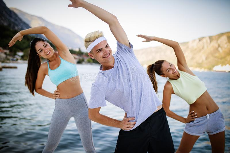 Fit group of happy people exercising outdoor. Smiling friends doing fitness workout stock image
