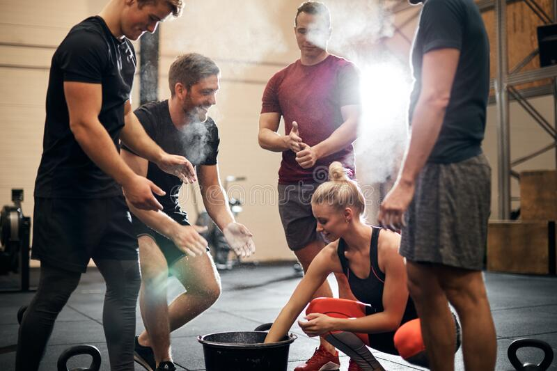 Smiling people chalking their hands before a gym workout stock photography