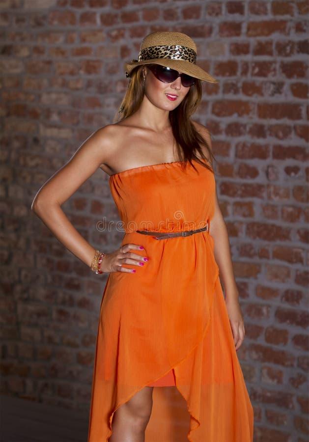 Fit härlig kvinna i orange klänning arkivfoto